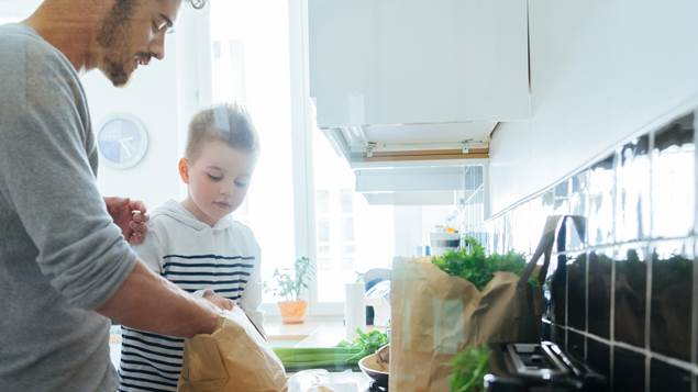 Father and son organizing groceries in kitchen