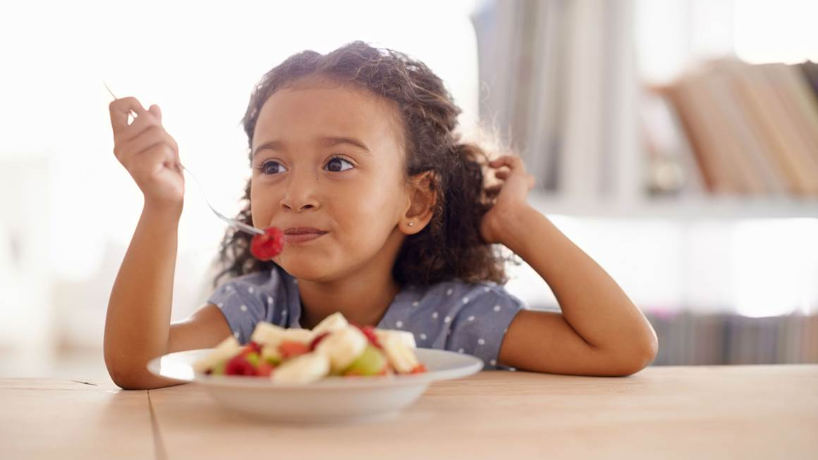 Girl eating fruit salad