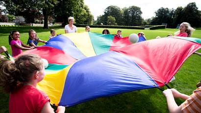 Kids and teacher playing with colourful parachute outdoors