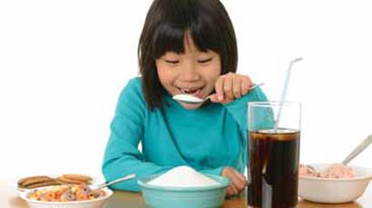 A smiling girl pretends to eat a large spoonful of sugar from a blue bowl