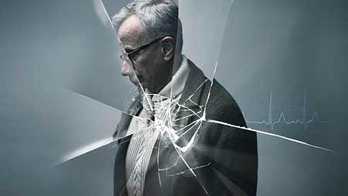Elderly man behind shattered glass
