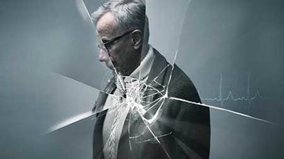 Elderly man behind shattered glass