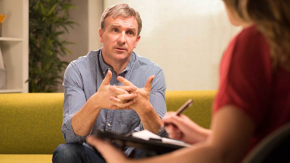 Man sitting on couch speaking to therapist