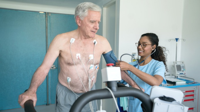 Nurse taking blood pressure of man on treadmill