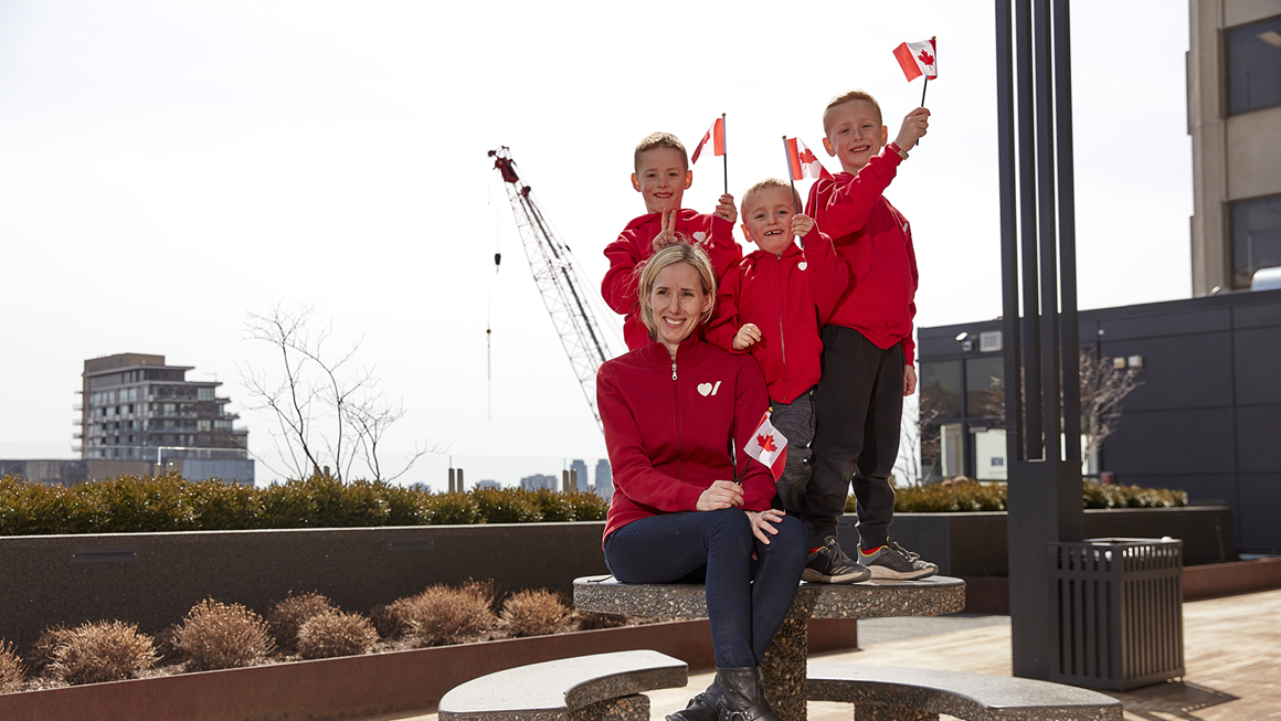 A mother and three young boys in Heart & Stroke sweatshirts wave Canadian flags.