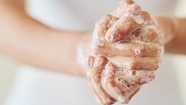 A woman washing her hands, zoomed in on her soapy grasp.