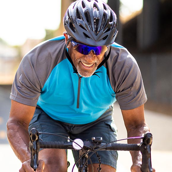 A smiling man in a blue jersey and bike helmet rides a bicycle.