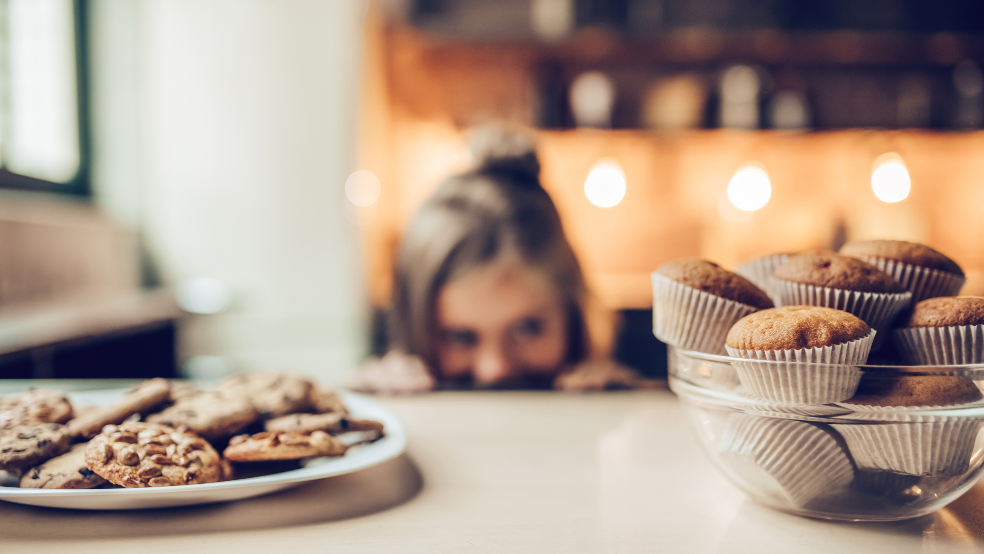 Little girl on the edge of the counter eyeing plates of cookies and muffins
