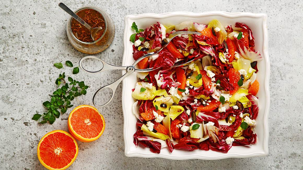 Radicchio, endive and citrus salad in a square serving dish with a cut orange and dressing on the side.