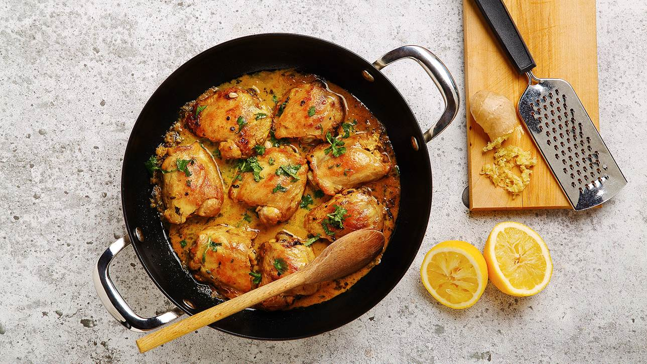 Curried lemon ginger chicken in a large skillet with grated ginger and cut lemon on the side.