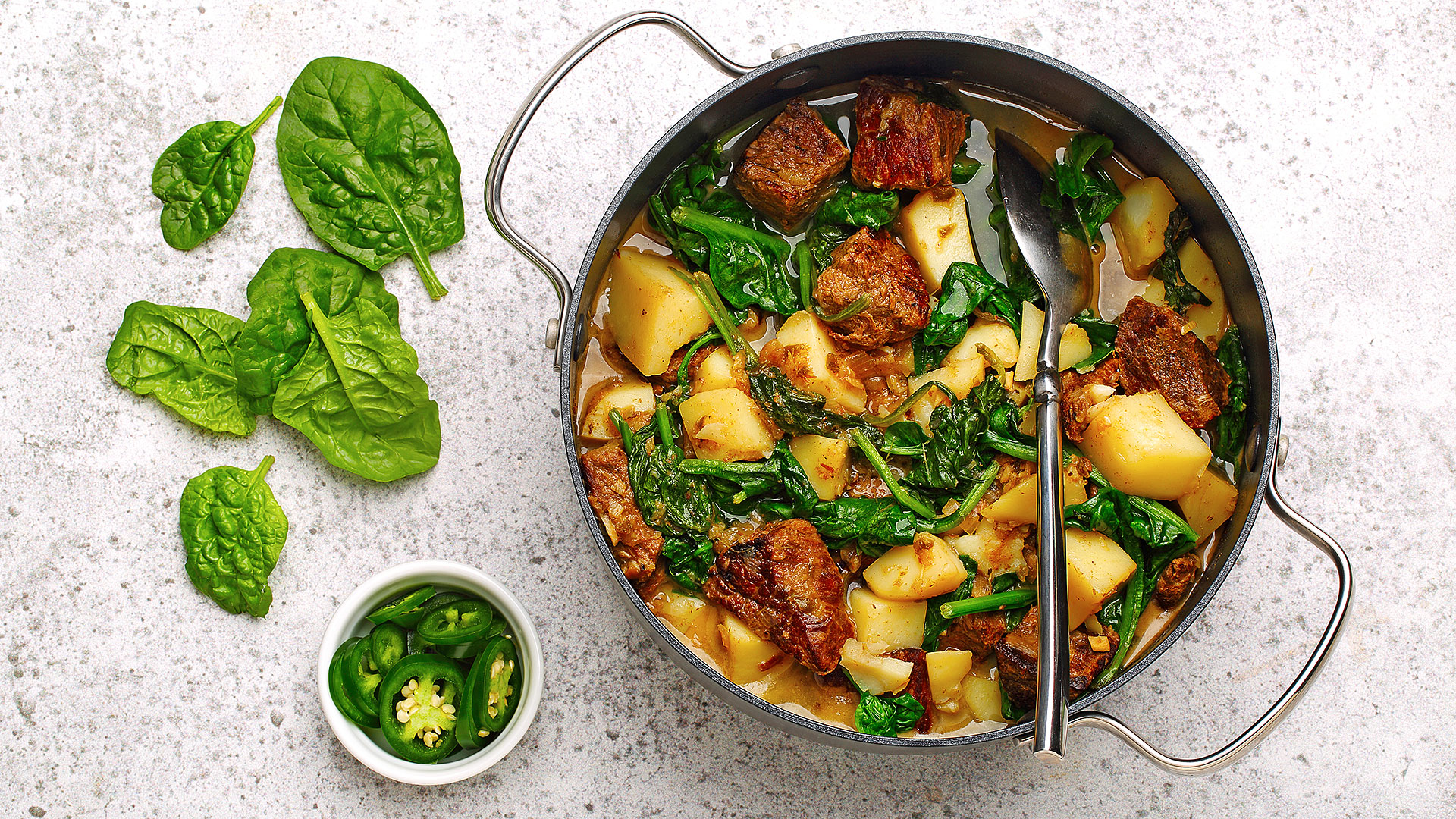 Spiced beef with spinach and potatoes in a skillet with sliced jalapenos and spinach leaves displayed on the counter beside it.