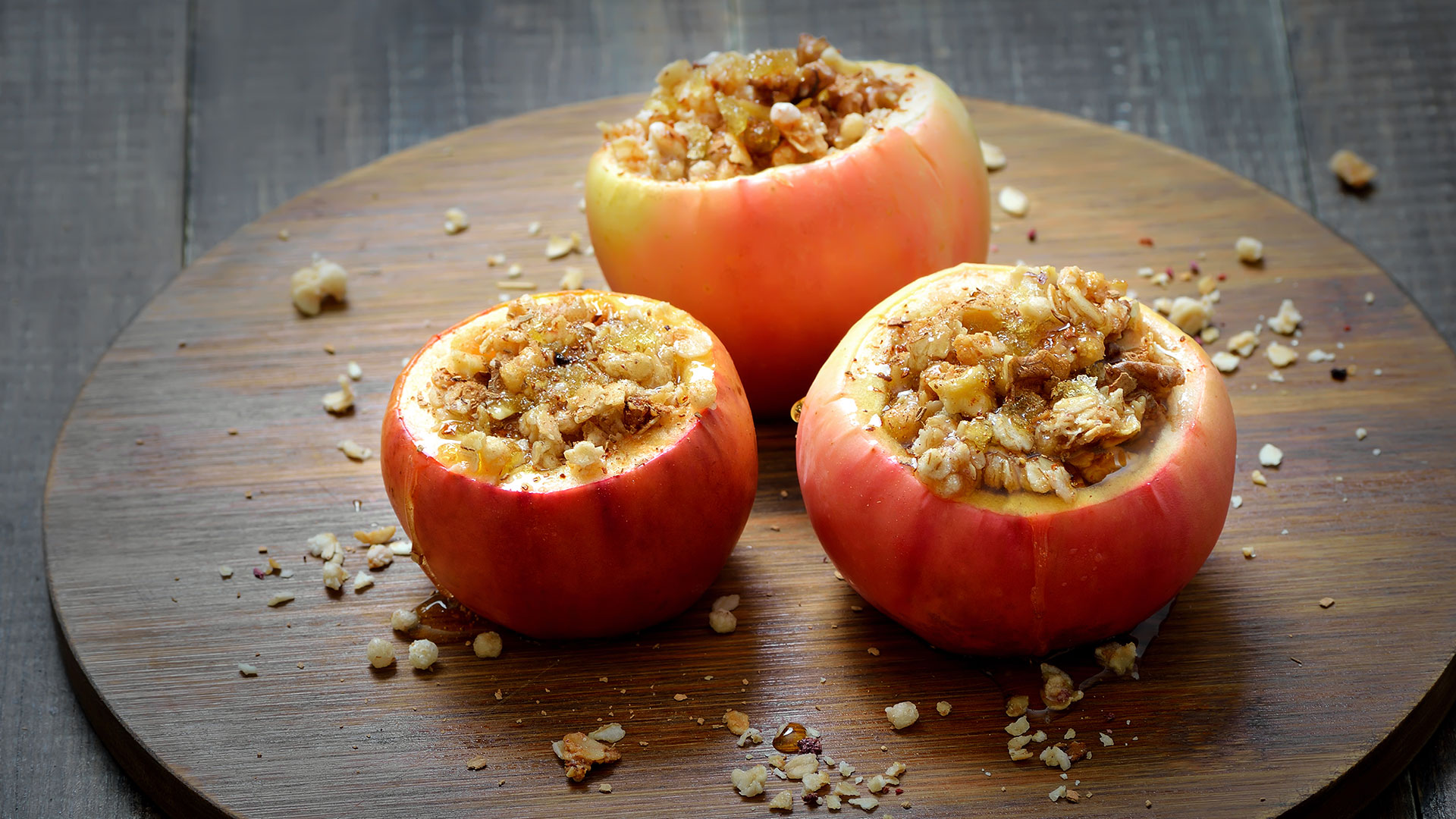 Three baked red apples on a wooden board with granola filling.