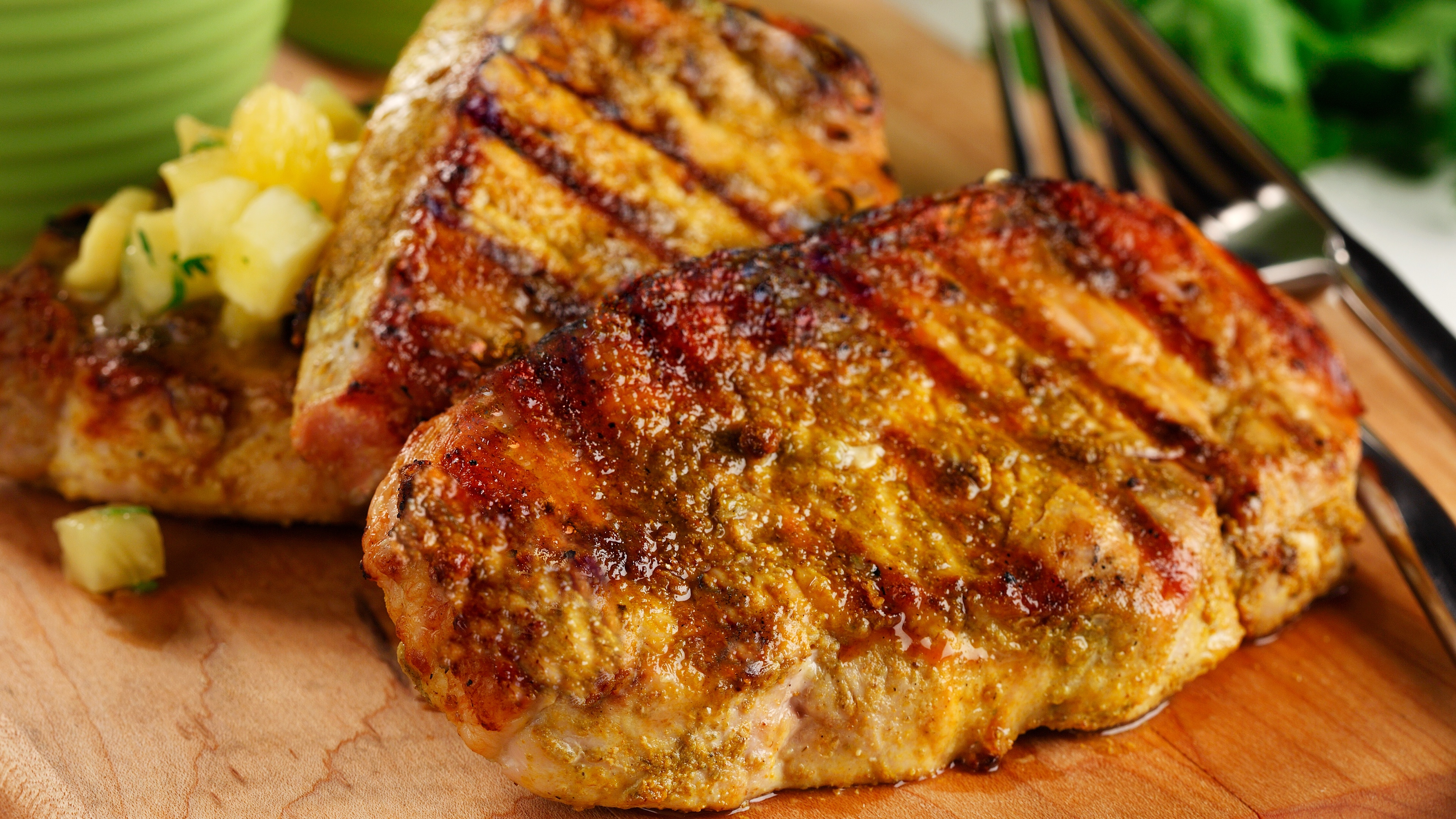 Close up of grilled pork chops on cutting board with sliced pineapple