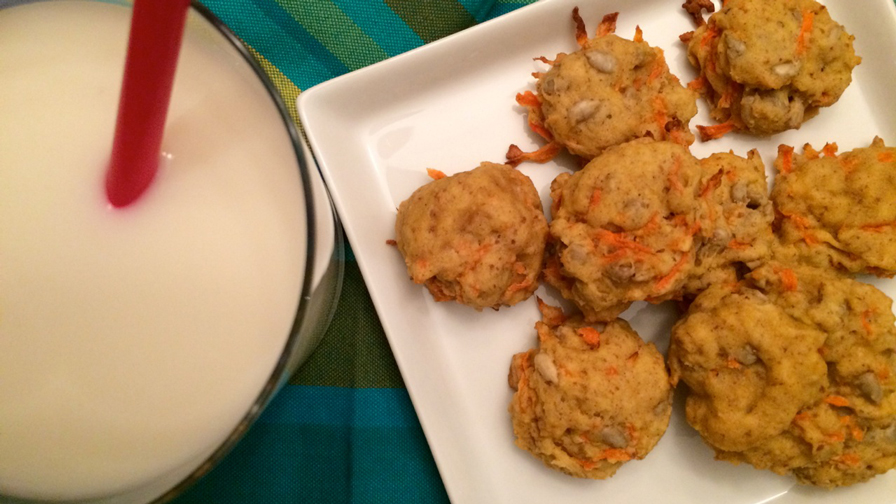Carrot cookies on a square white plate with a glass of milk with a red straw on the side