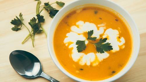 Carrot squash soup with cream and a parsley sprig in a white bowl on a wooden board next to a metal spoon.