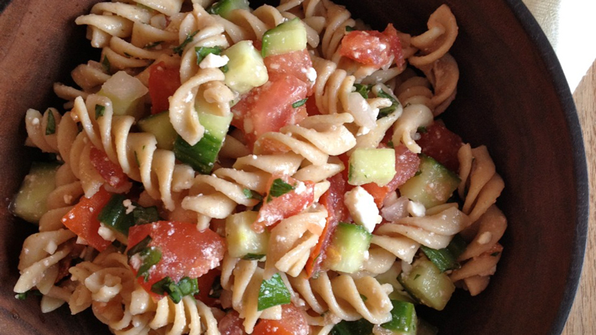 Chunky cucumber and tomato gazpacho pasta salad in a wooden bowl