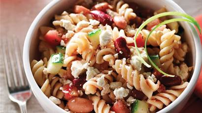 Fusilli salad with salsa and feta in a white bowl with a fork beside.