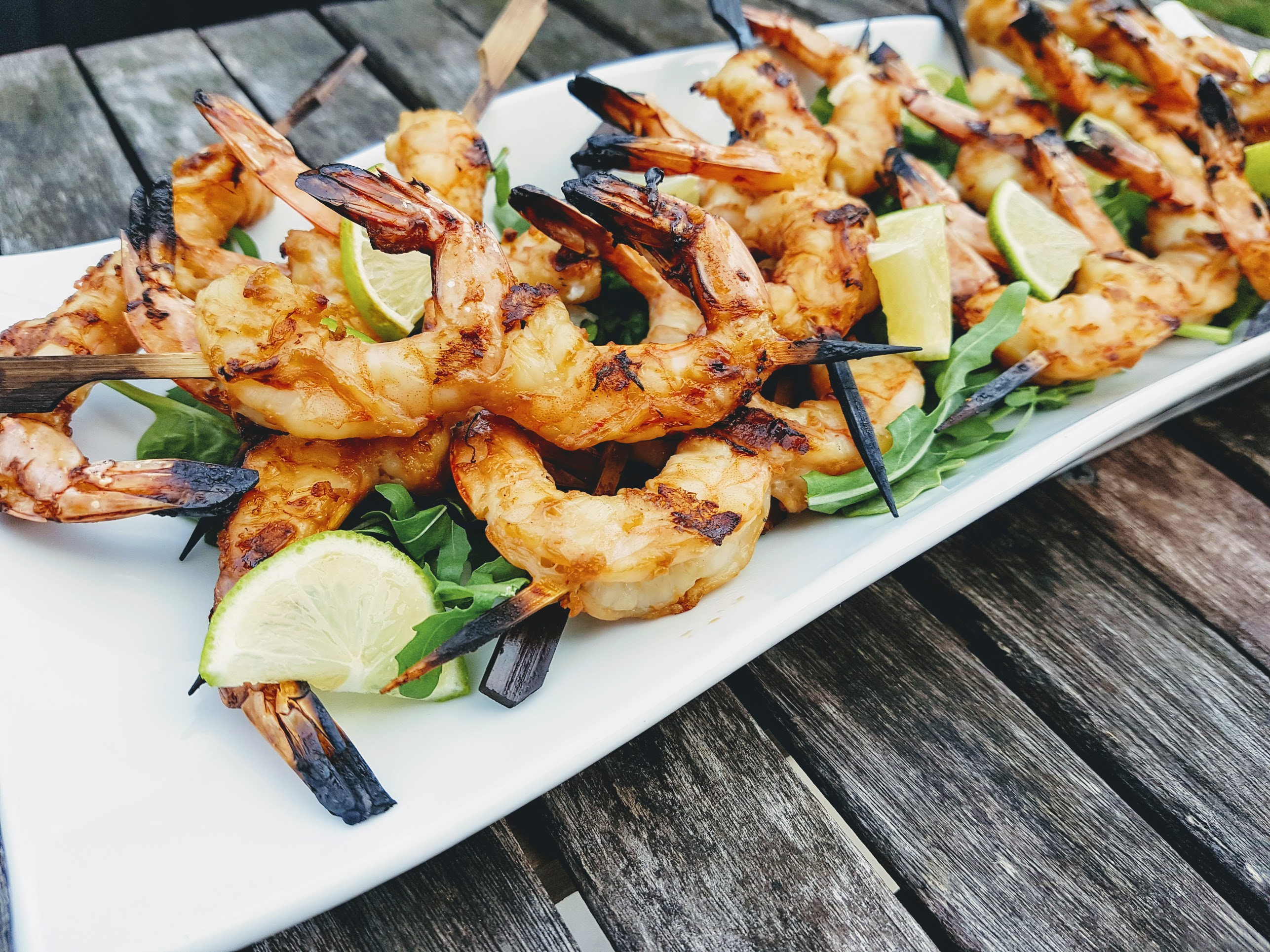 Pile of grilled shrimp skewers on a bed of arugula