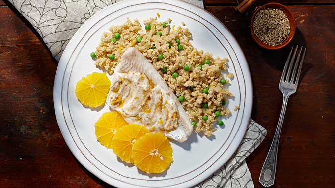 Moroccan spiced fish and couscous on a white plate with orange slices