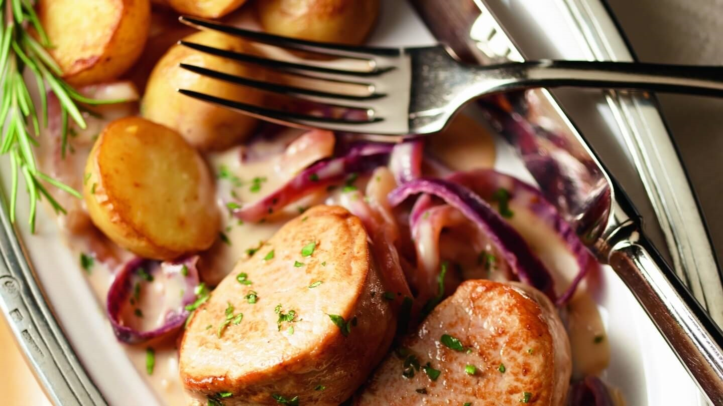 Pork medallions with roasted potatoes and red onions on silver platter