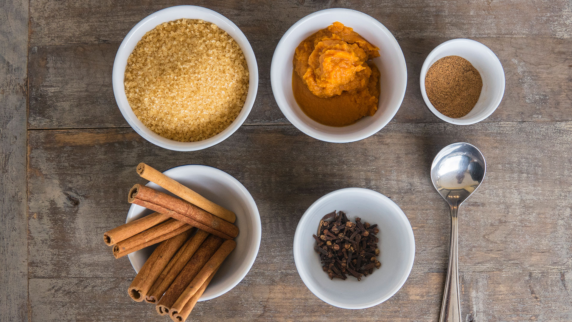 Pumpkin spice ingredients in white bowls and a serving spoon on a wooden tabletop.