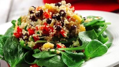 Cooked quinoa, chopped red peppers, mango and black beans on a bed of spinach