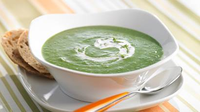 Spinach and green pea soup in a white bowl with a yellow spoon