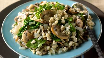 Spinach and mushroom barley pilaf served on a blue plate with a spoon on the side