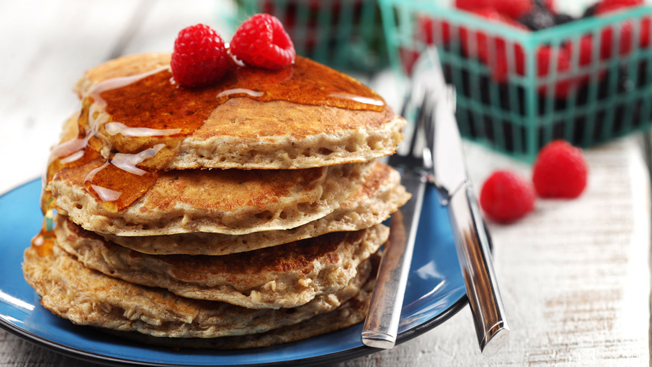 Stack of pancakes on a blue plate topped with raspberries