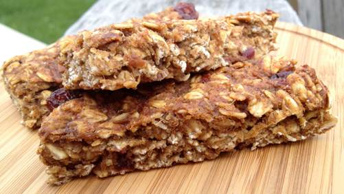 Three cranberry granola bars on a wooden cutting board
