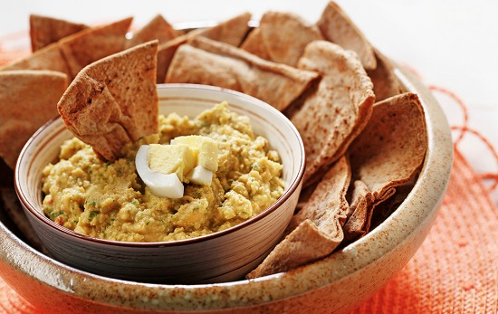 protein powered hummus with hard boiled egg in bowl with whole wheat pita bread