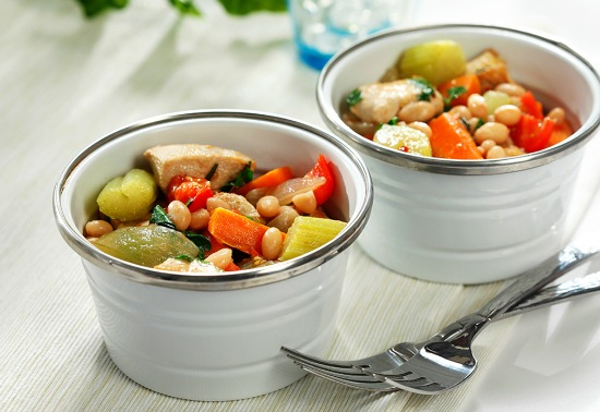 Two white bowls filled with cooked chicken, celery, carrots, navy beans and broth