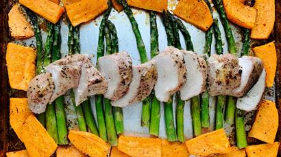 Pork tenderloin on a baking sheet with sweet potatoes and asparagus