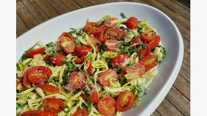 Plate of spiralled zucchini noodles, sliced cherry tomatoes and basil