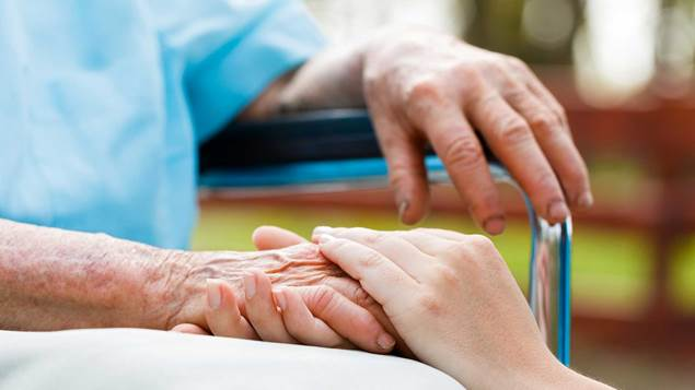 Doctor holding elderly patients hand in a wheel chair