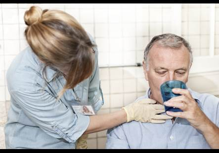 A man drinks water out of a cup with the help of a nurse.