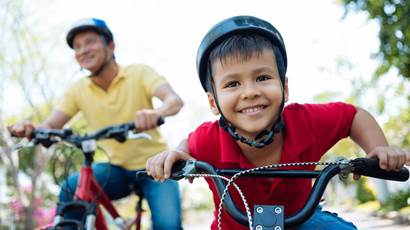 Little boy wearing helmet riding bicycle