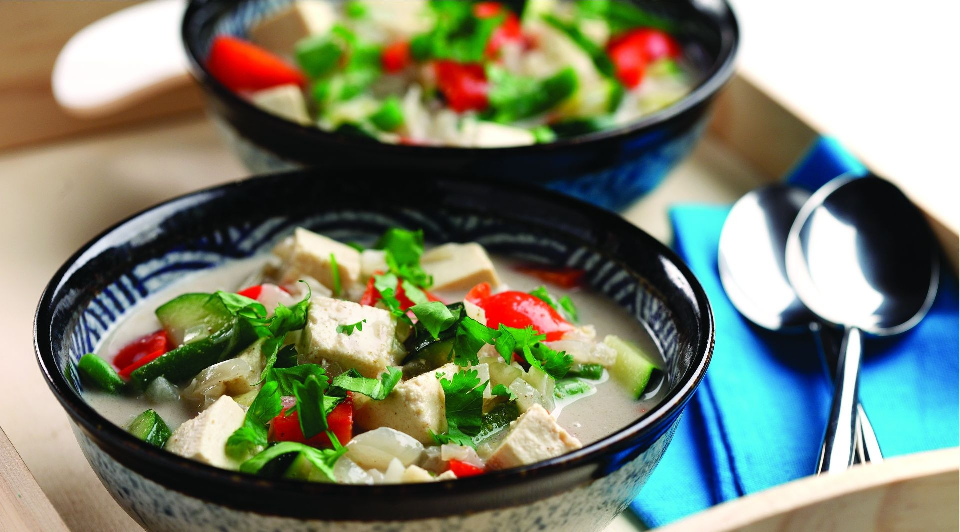 Bowls of tofu cubes, cilantro, red pepper, zucchini and broth
