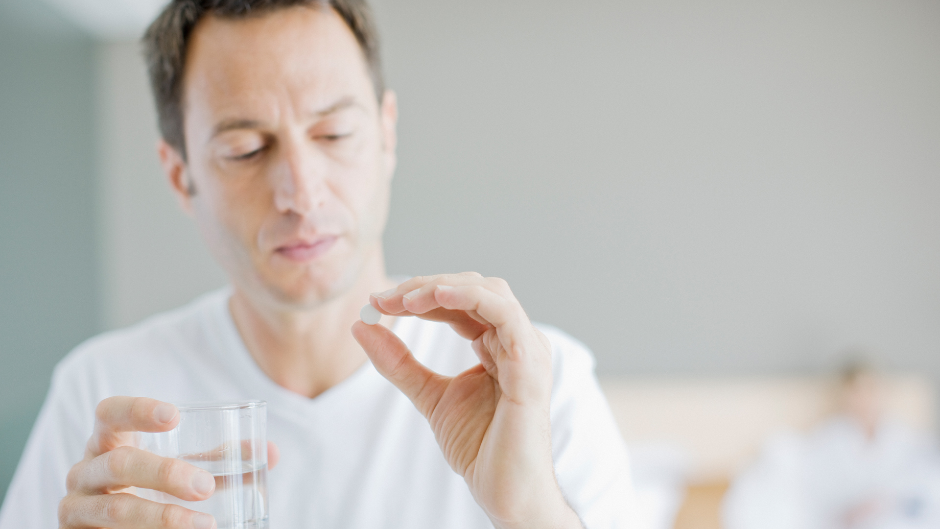 Man in white t shirt holding aspirin and glass of water