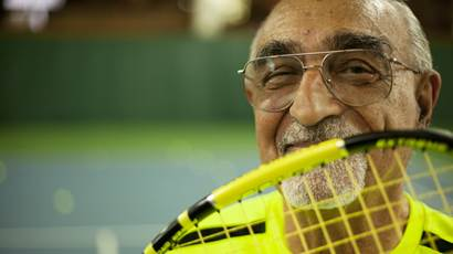 Marco smiling with tennis racquet