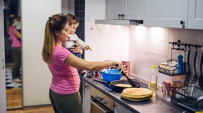 mother holding baby in kitchen cooking crepes