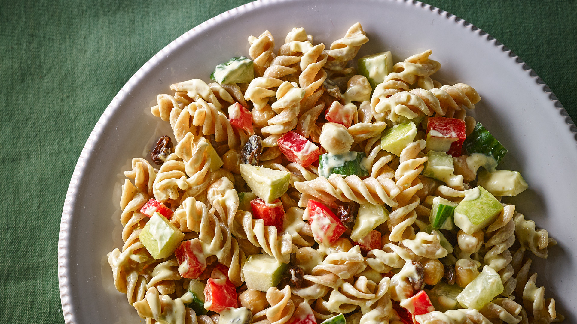 Pasta salad with cucumbers, red peppers, raisins and yogurt dressing