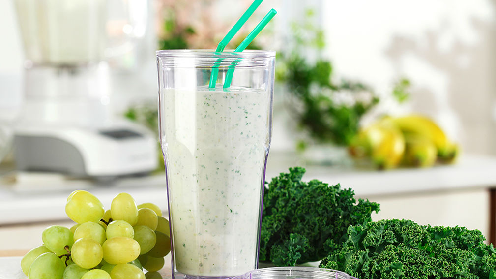 Smoothie in glass on kitchen counter with green grapes and kale.