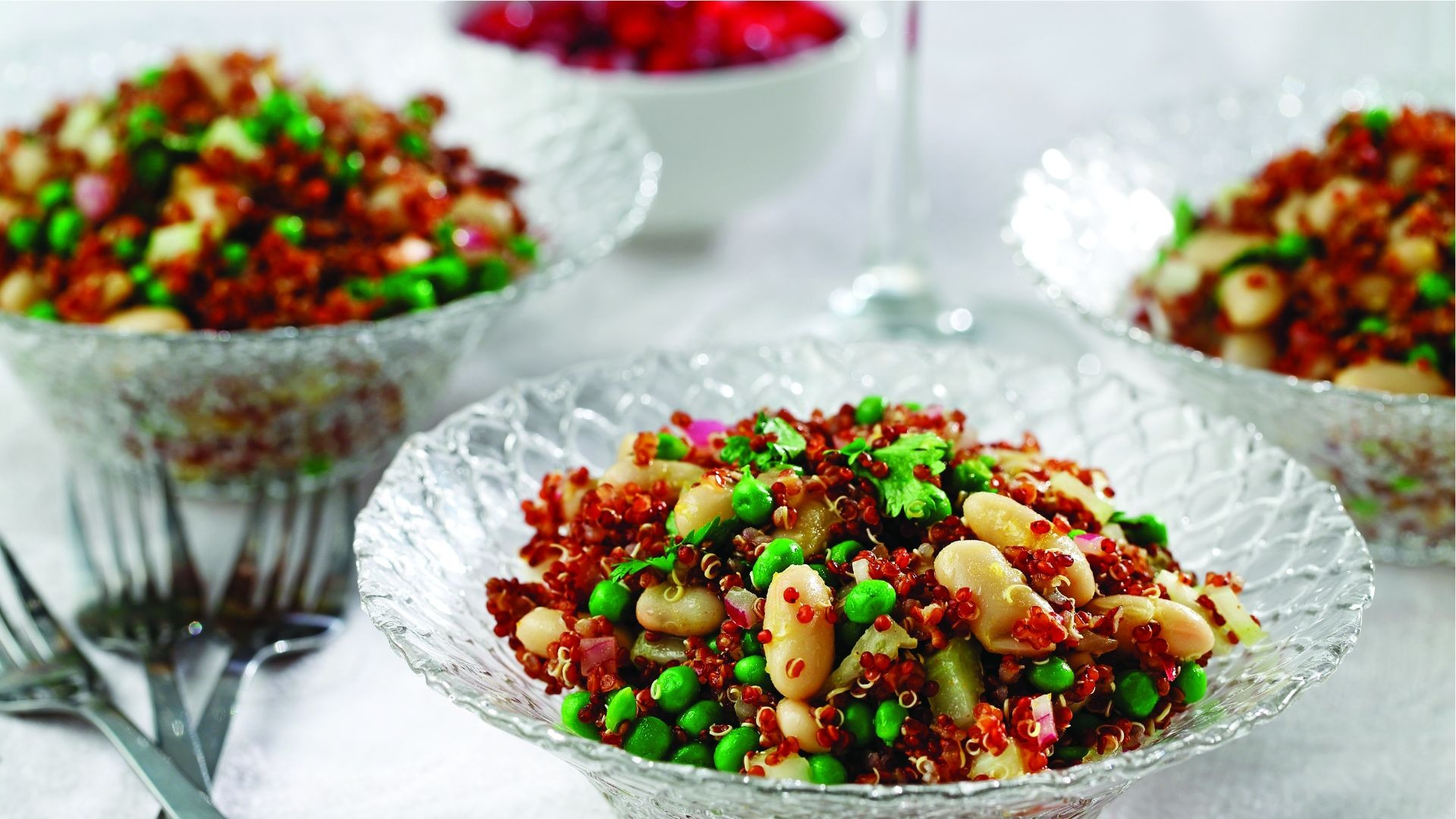 Glass bowls filled with quinoa, cannellini beans, peas and cilantro