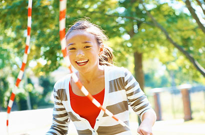 A smiling young girl skips outdoors with a skipping rope.