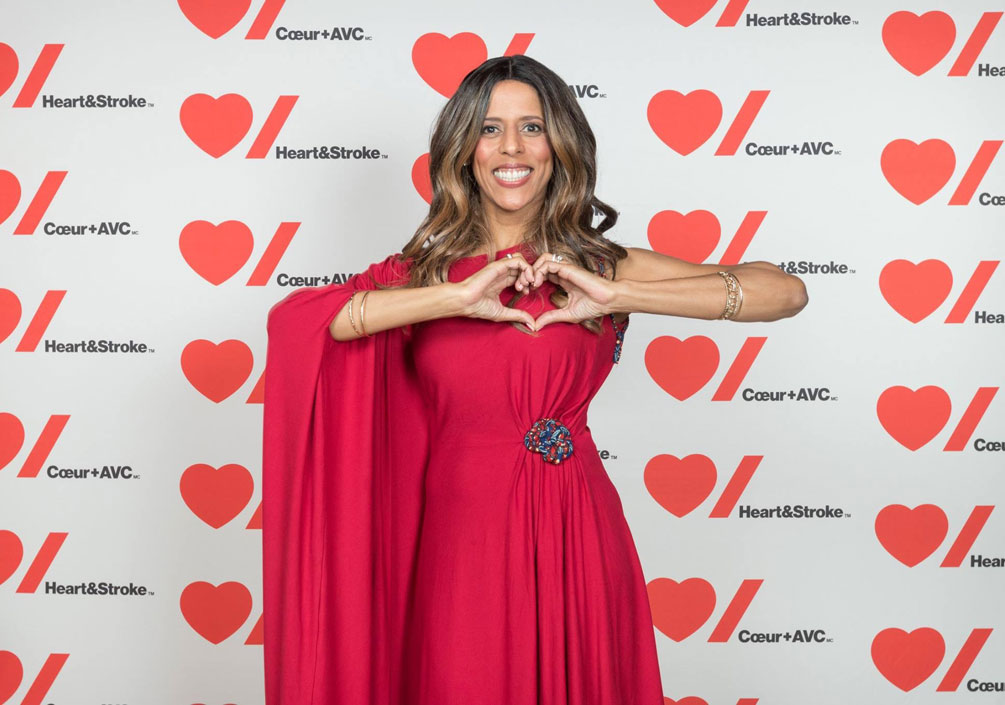 Caroline Lavallée wears a red gown and holds her hands in a heart shape.