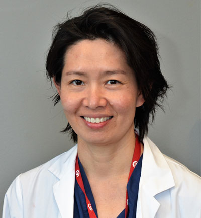 Dr. Sharon Chih in a white lab coat