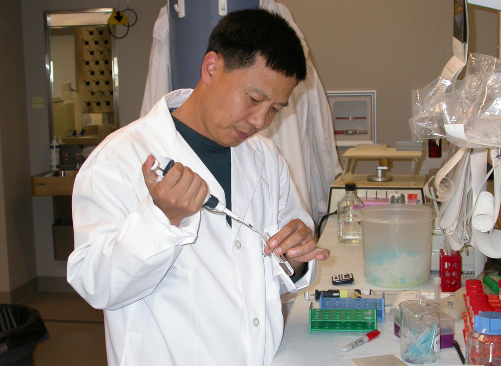Dr. Wang in his lab in a white lab coat