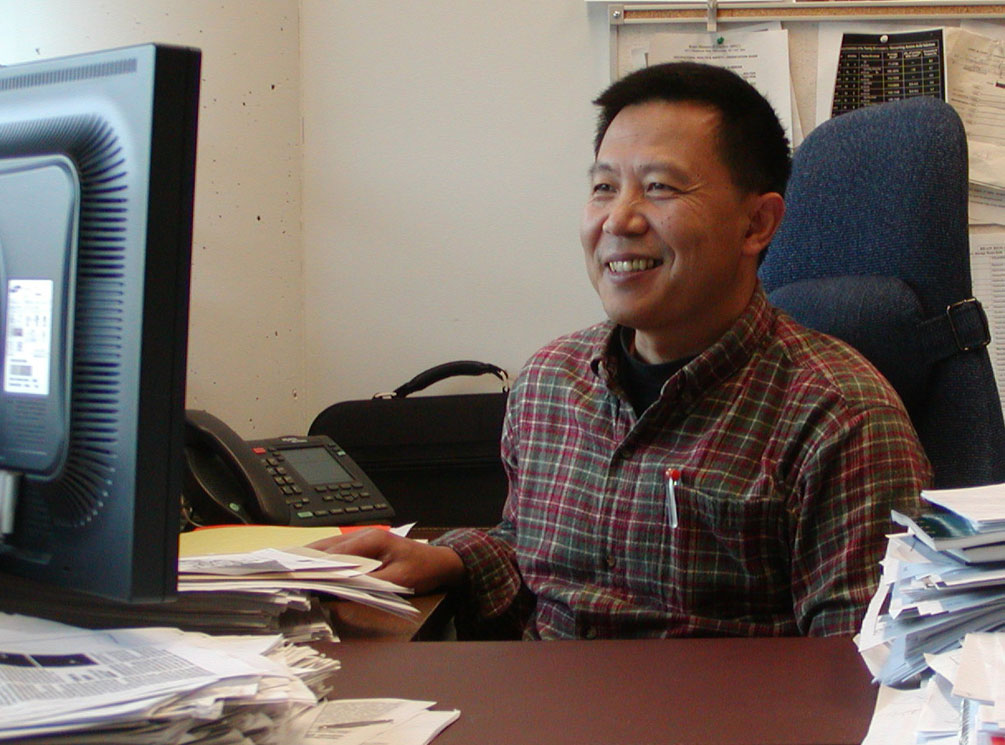 Dr. Wang sitting in front of his computer smiling.