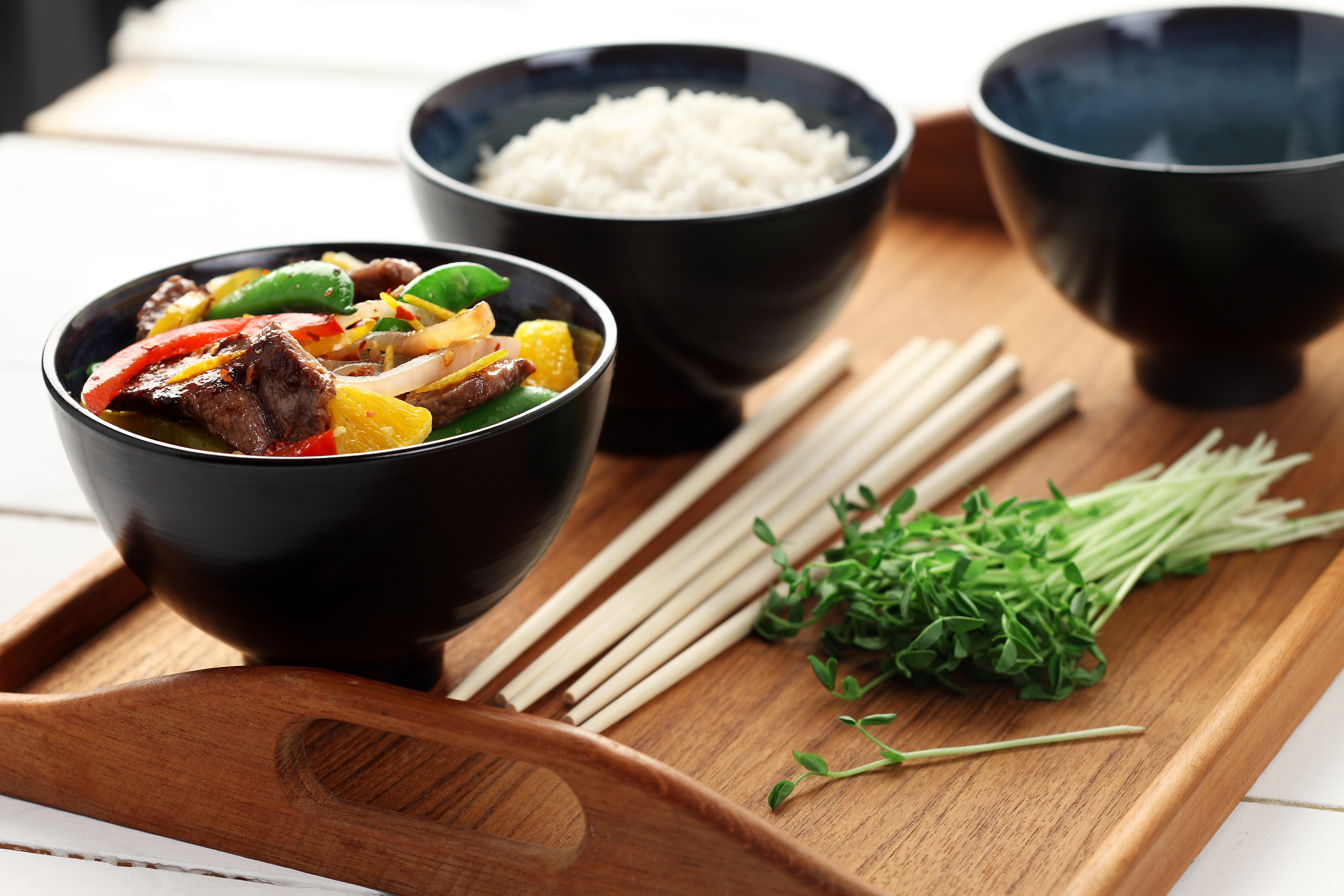 Spicy beef with oranges in black bowls on a wooden tray